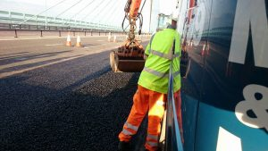 clamshell bucket removing excess tarmac from carriageway on Severn bridge